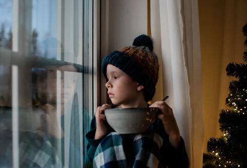 Young boy sat on a window sill with a cereal bowl looking outside - CAVF76340