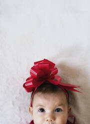 Portrait of baby girl with red ribbon on her head looking up - GEMF03482