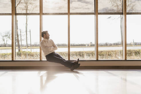 Businessman sitting at the window in open-plan office - DIGF09482