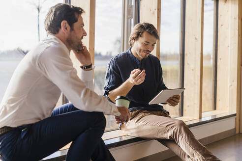 Two businessmen with tablet talking at the window in open-plan office - DIGF09485