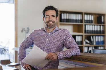 Portrait of smiling businessman with document in wooden open-plan office - DIGF09497