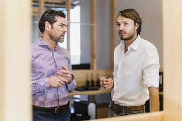 Two businessmen talking in wooden open-plan office - DIGF09521