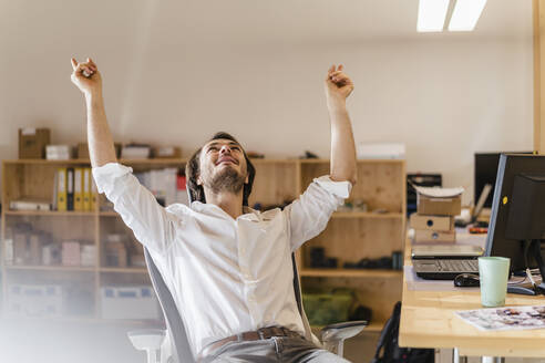 Businessman cheering at desk in office - DIGF09533