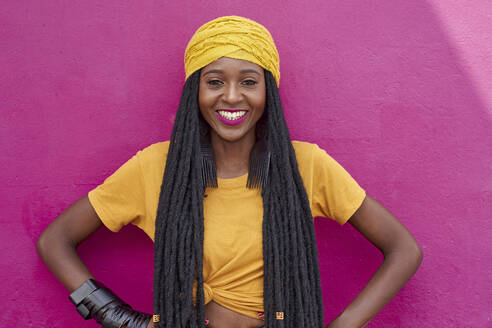 Portrait of woman with long dreadlocks in front of a pink wall - VEGF01677