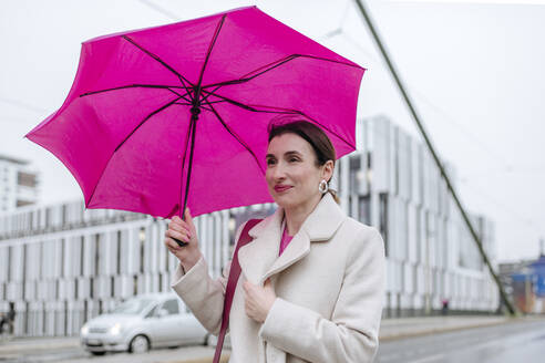 Smiling woman with pink umbrella walking in the city - VYF00052