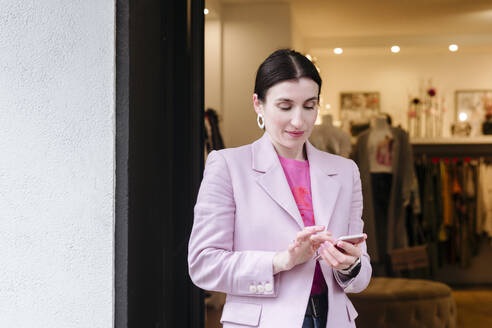 Stylish woman in pink jacket using smartphone - VYF00055