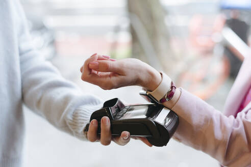 Hand of woman, paying cashless at POS terminal with her smartwatch - VYF00061