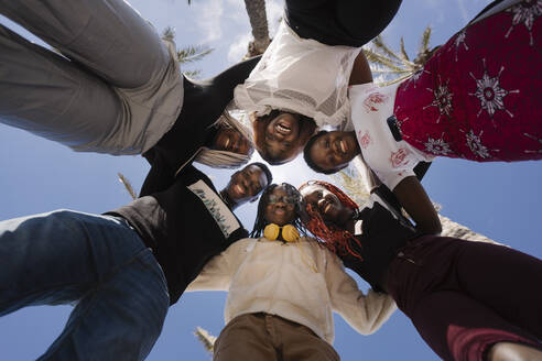 Portrait of happy teenage girlfriends and young man huddling under blue sky - MPPF00602