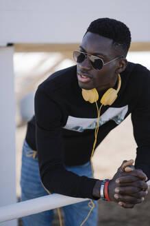 Stylish young man wearing sunglasses looking around - MPPF00608