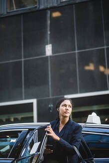 Female entrepreneur looking away while coming out from car - MASF16950