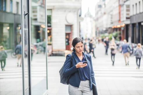 Businesswoman using phone while standing in city - MASF16962