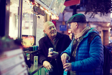Senior gay couple standing against concession stand in city at night - MASF17115