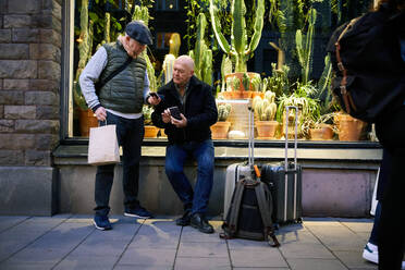 Full length of senior gay couple using mobile phone while waiting outside plant store at night - MASF17121