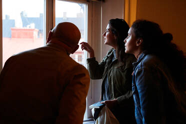 Women looking through window while standing with male owner at home - MASF17124