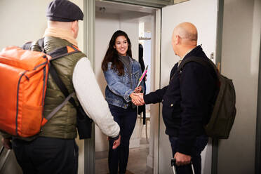 Smiling woman handshaking with senior man while standing with friend at doorway - MASF17133