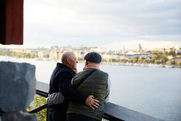 Rear view of gay couple with arm around standing against railing by river in city - MASF17142