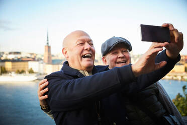 Smiling gay couple taking selfie with mobile phone against river in city - MASF17145