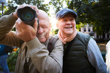Senior man using camera while standing with friend at park in city - MASF17148