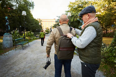 Senior man adjusting bag strap of friend while standing at park in city - MASF17154