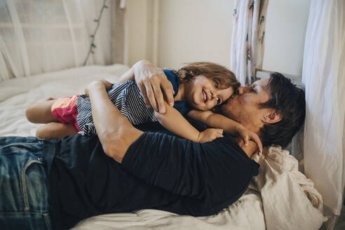 Mature father kissing daughter while lying on bed - MASF17244