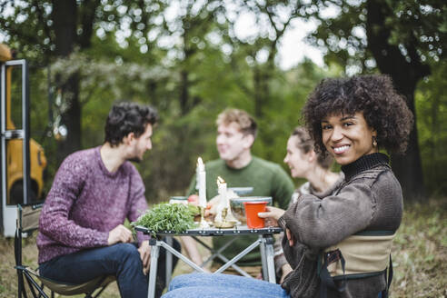 Portrait of smiling Afro woman sitting with friends at table during camping in forest - MASF17286