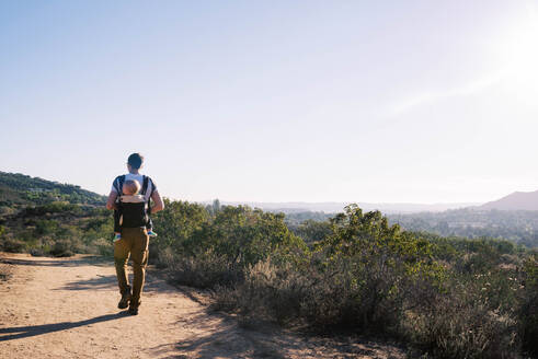 Millennial father hiking with his son on his back. - CAVF76995