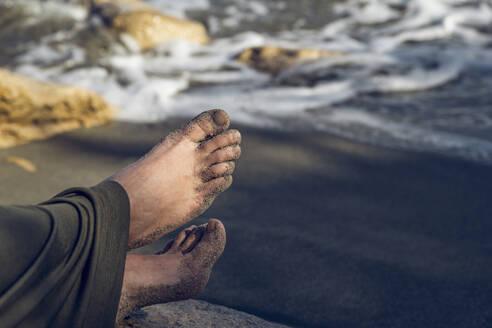 Bare feet with sand, sitting on beach near Triopetra, Creta, Greece - MAMF01252