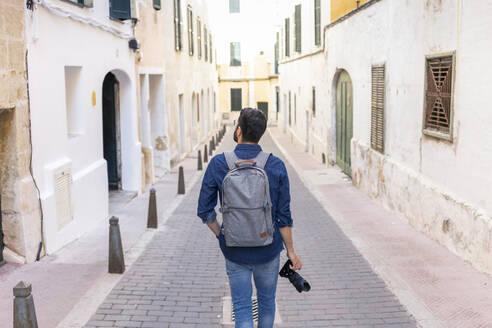 Back view of man with camera exploring the city, Mao, Menorca, Spain - JPTF00476