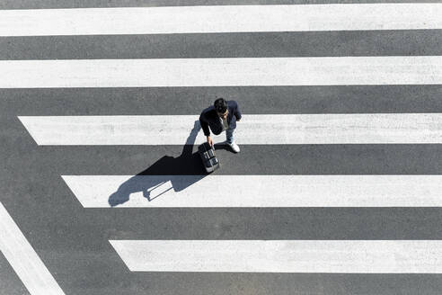 Man on zebra crossing pushing his trolley bag, top view - JPTF00479