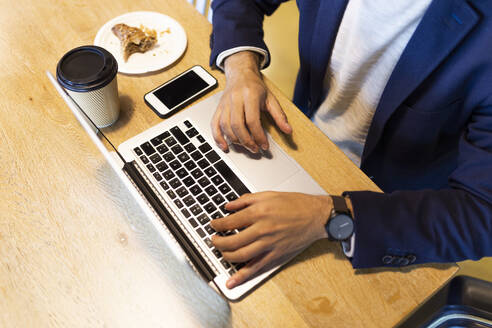 Crop view of businessman working on laptop in a coffee shop - JPTF00485