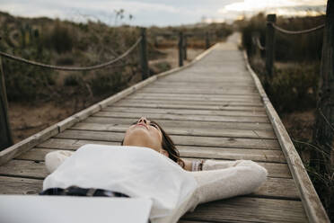 Woman lying on a boardwalk in the countryside with laptop - JRFF04156