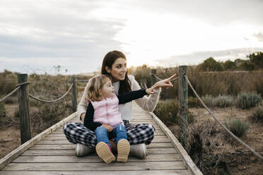 Happy mother and daughter sitting on a boardwalk in the countryside - JRFF04162