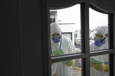 Scientists wearing protective clothing informing people at the door - KMKF01235