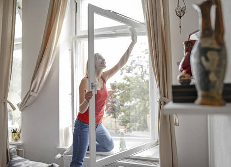 Smiling young woman cleaning window at home - BFRF02202