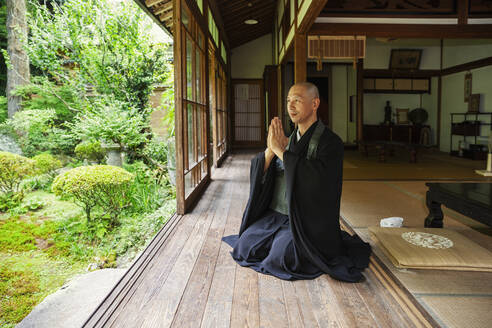 Buddhist priest kneeling in Buddhist temple, praying. - MINF14118