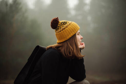 Thoughtful woman sitting by forest in foggy weather - CAVF77067