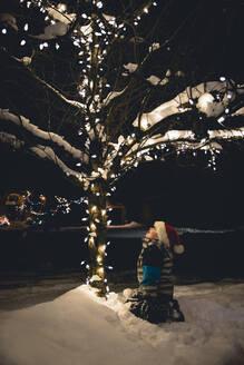 Boy in Santa hat sitting in snow looking at Christmas lights on tree. - CAVF77088