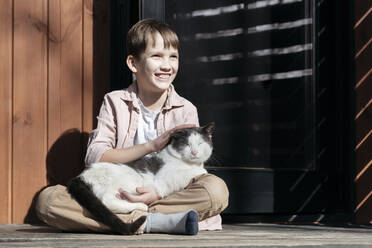 Smiling boy looking away while stroking cat relaxing on him at porch during sunny day, Tarusa, Russia - EYAF00951