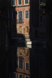 Italy, Venice, House illuminated by last rays of setting sun reflecting on surface of canal - MRAF00497
