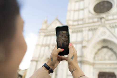 Woman taking smartphone picture of Santa Croce church, Florence, Italy - FMOF00905