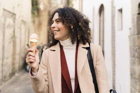 Happy woman eating an ice cream cone in an alley, Florence, Italy - FMOF00923