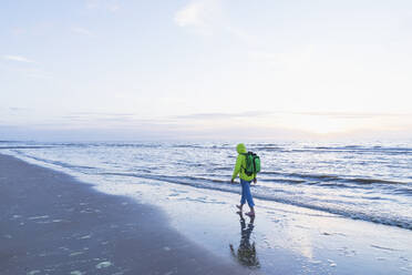 Retired senior man with backpack walking on shore at beach during sunset, North Sea Coast, Flanders, Belgium - GWF06548