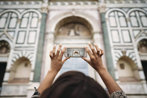 Close-up of young woman taking a smartphone picture in the city, Florence, Italy - JPIF00469