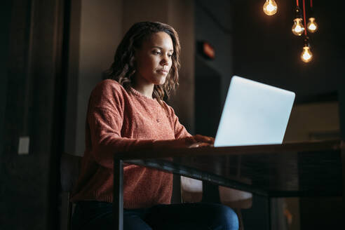 Young woman using laptop in a cafe - JPIF00484