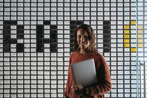 Portrait of young woman holding laptop at a wall with the word 'radio' - JPIF00487