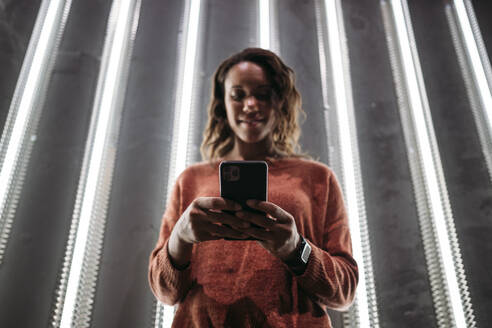 Young woman using smartphone at illuminated wall - JPIF00490