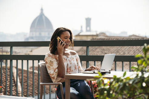 Young woman using laptop and talking on the phone on a balcony in Florence, Italy - JPIF00496