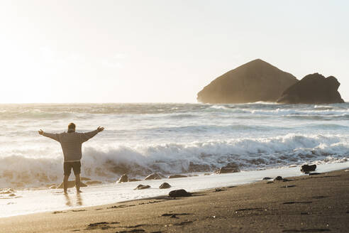 Man standing on the beach at sunset with outstretched arms, Sao Miguel Island, Azores, Portugal - AFVF05705