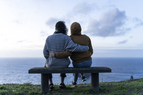 Couple sitting on a bench at the coast at sunset, Sao Miguel Island, Azores, Portugal - AFVF05708
