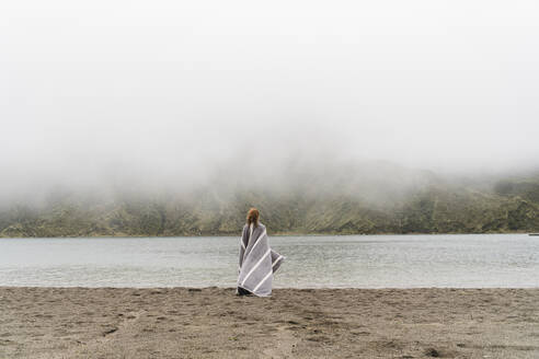 Woman wrapped in blanket standing at lakeshore in Sao Miguel Island, Azores, Portugal - AFVF05712
